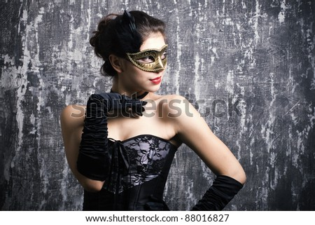 Stock Photo The beautiful young girl in a mysterious mask