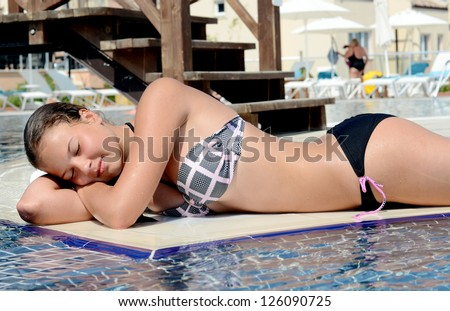 The beautiful  young girl  relaxing in pool