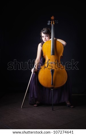 the beautiful young girl with a violoncello against a dark background