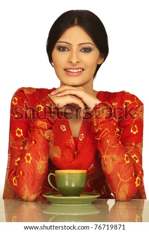The beautiful young Indian woman drinks coffee or tea