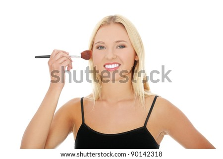 The beautiful young woman does a make-up, isolated on a white background