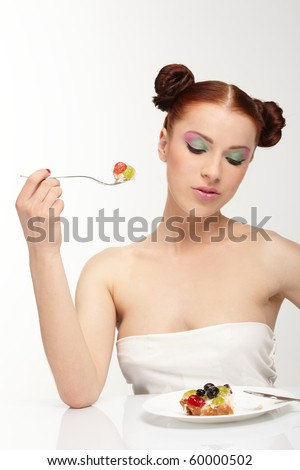 The beautiful young woman eat tasty cake
