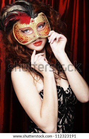 The beautiful young woman in a red mysterious  mask