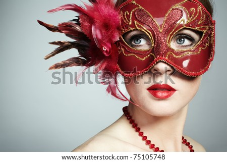 The beautiful young woman in a red mysterious venetian mask
