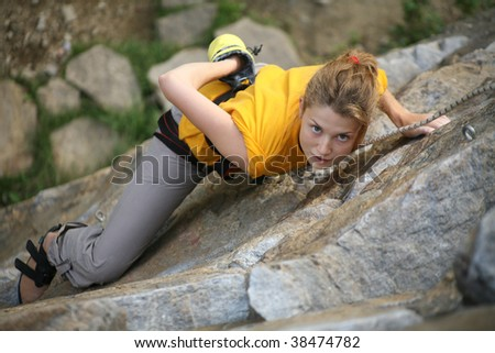 The beautiful young woman rises on a rock