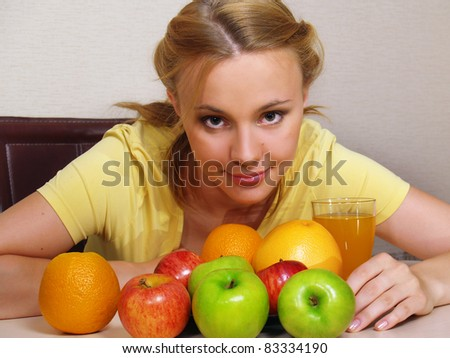 The beautiful young woman sits at a table with colorful fruits