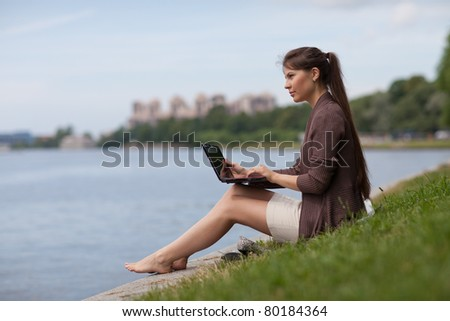 The beautiful young woman sits on a grass in the park with the laptop.