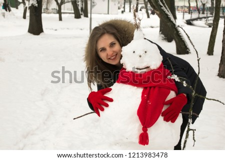 Stock Photo The beautiful young woman the blonde with blue eyes embraces a snowman. The snowman is dressed in a red scarf. The woman is dressed in red gloves. The woman is in the winter park.