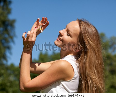 The beautiful young woman with camomile  against of blue sky. Fortune-telling on a camomile.