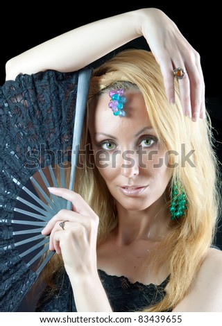 The beautiful young woman with long  blonde hair and  fan and jewellry on  dark background