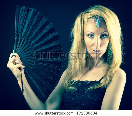 The beautiful young woman with long  blonde hair and  fan on  dark background,with a retro effect