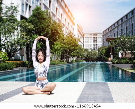 The beauty lady is sitting beside swimming pool.she is raise her hands up,close eyes and breath with relax feeling,posing basic yoga pattern,blurry light around.