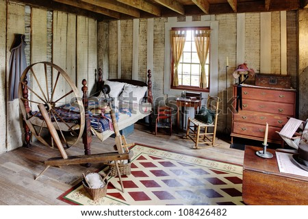 The bed room in a primitive colonial style reproduction home, built with materials reclaimed from structures built in the late 1700's.  The room contains many antiques from the late 18th century.