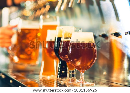 The beer taps in a pub. nobody. Selective focus. Alcohol concept. Vintage style. Beer craft. Bar table. Steel taps. Shiny taps. Glass of beer. Octoberfest concept