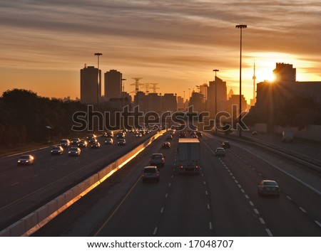 The beginning of morning rush hour, cars on the highway traveling to and from  downtown