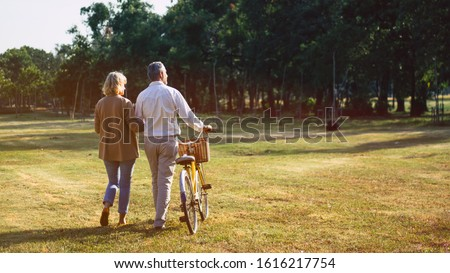 The behind of Caucasian elderly couples walking with a bicycle in the natural autumn sunlight garden feel cherish and love, concept elderly love, warm family, happy retirement, retirement lifestyle.