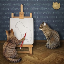 The beige cat artist with a pencil is drawing his friend on an easel in the workshop.