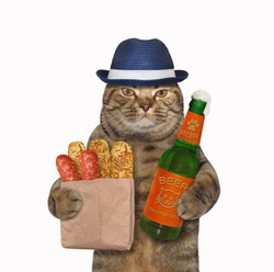 The beige cat in a blue hat is holding a opened bottle of beer and a paper bag with sausage and cheese breads. White background. Isolated.
