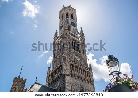 The belfry of Bruges on a summer day, surrounded by a beautiful, milky blue sky. The sun hiding behind the belfry.  Stock photo ©