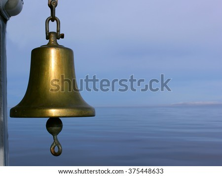 The bell at front with the still water and the blue cloudy sky with the clear horizon on the background at the silent late evening. #375448633