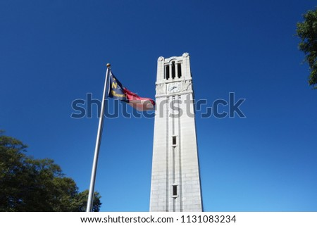 The bell tower and North Carolina state flag on the campus of NC State University