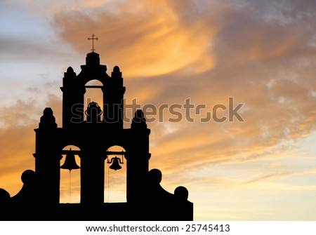 The bell tower of an authentic 1700's Spanish Mission in silhouette against a colorful sunset sky (Christian/Easter/Church image).