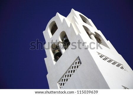 The bells of a white washed church in Santorini Greece