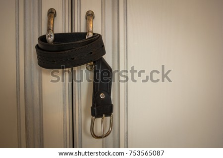 The belt hangs on the handle of the closet in the children's bedroom. The use of physical force, intimidation, domestic terror. #753565087