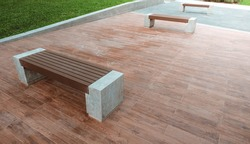 The bench is made of concrete and artificial wood, placed on a wood-patterned tile floor.