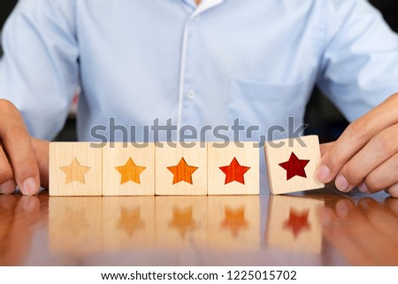 The best and excellent business services rating. Businessman hand putting wooden five star shape on table.  Customer experience survey  concept. #1225015702