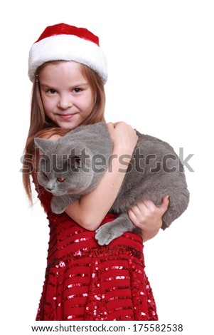 The best christmas present ever - happy little girl with her new cat isolated on Holiday theme/little santa hat holding cat on holiday theme