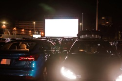 The best place to go. Many cars parked in front of a big white screen to watch movies or films sitting inside the car at drive in cinema in the evening. Entertainment, hobby concept