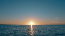 The best sundown over the sea. Natural sunset landscape. Blue sea and blue sky background. The sun on the horizon. Sundown in the ocean.