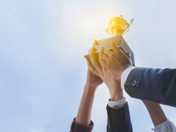 The best team helped each other reach their goals target to success. The hand of a business man and business women pick up the trophy and celebrate together. Teamwork of successful concept
