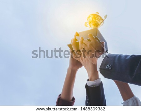 The best team helped each other reach their goals target to success. The hand of a business man and business women pick up the trophy and celebrate together. Teamwork of successful concept #1488309362