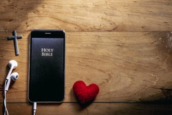 The Bible app in smart phones with red heart and silver cross on a wooden table, read and listen to the voice of God, Headphone, Close up, christian concept.