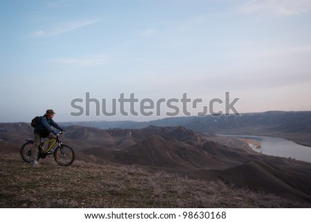The bicyclist on hilly district looks downwards at the river