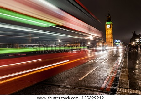 The Big Ben at night, london, UK with a typical bus passing by