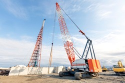 The big crawler crane and other construction machineries are working to build pier of the harbor. A crawler crane has its boom mounted on an undercarriage fitted with a set of crawler tracks.