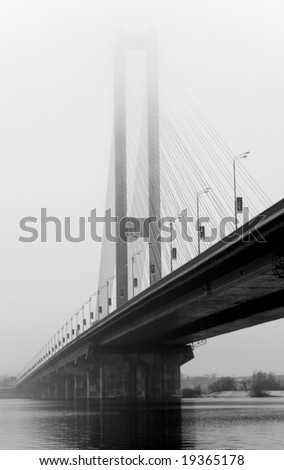 the big river bridge with steel cable support, piers, arch out of fog black white image