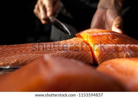 The big salmon is in the hands of the experienced Japanese chef.He is using a knife to slice salmon fillet for sashimi and sushi.