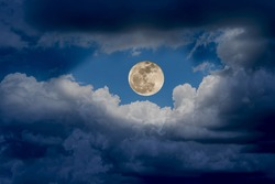 The big super moon shines wonderfully with the white clouds in the sky at night, nature background.