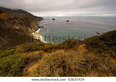 The big sur coast line often is enshrouded in fog which rolls in quite frequently. - stock photo