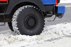 The big wheel of a AWD fire truck drives off the road into a snowdrift on a winter day closeup