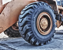The big yellow wheel of heavy tractor