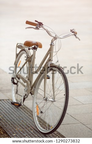 The bike parked on the streets of European cities. Conceptual image of a healthy lifestyle and environmental form of transport. Retro beige bicycle outdoors