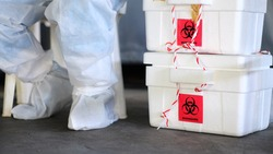 The biohazard box stores a swab test covid-19 and a doctor wearing a PPE protective suit.