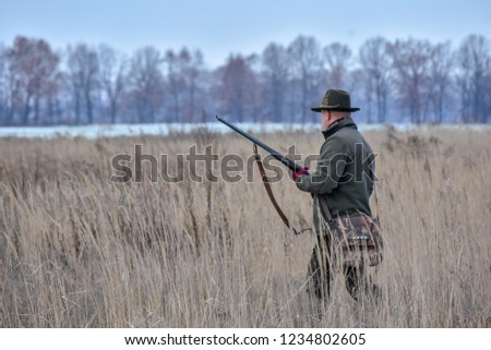The bird hunter walks through the field with his dog on a partridge hunt
