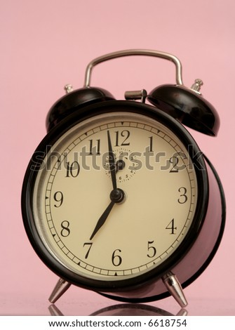 The black alarm clock is on a pink background
