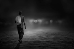 The black and white image of a young man wandering on the road in the night alone